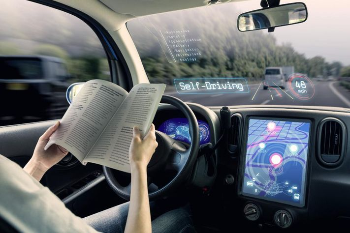 buồng lái của xe tự trị. một chiếc xe chạy chế độ tự lái và một phụ nữ lái xe đọc sách.